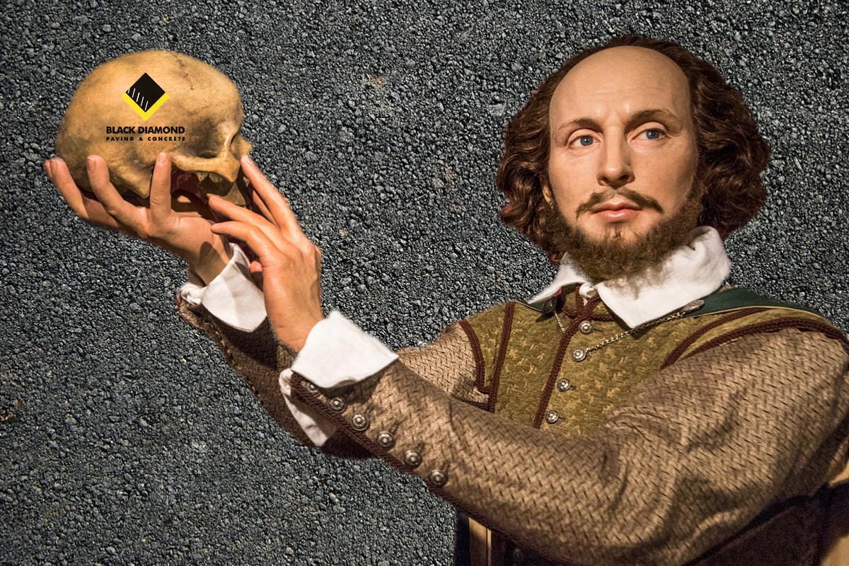 Realistic wax figure of Shakespeare holds skull with Black Diamond Paving logo on it